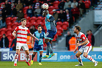 Adebayo Akinfenwa of Wycombe Wanderers (centre) heads the ball during the Sky Bet League 2 match between Doncaster Rovers and Wycombe Wanderers at the Keepmoat Stadium, Doncaster, England on 29 October 2016. Photo by David Horn.