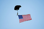 A member of the Special Forces Association Parachute Team flies into Coach Joe Popp Stadium carrying the American Flag prior to the start of the Patriot Bowl between the A.L. Brown Wonders and the Mooresville Blue Devils on September 9, 2016, in Mooresville, North Carolina.  The Blue Devils defeated the Wonders 23-21.  (Brian Westerholt/Special to the Tribune)