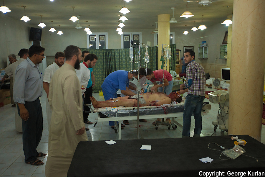 10/08/2012, Assas FSA Field Hospital: <br /> Ahlam Saleh's uncle unconscious with multiple injuries and broken bones being attended to.