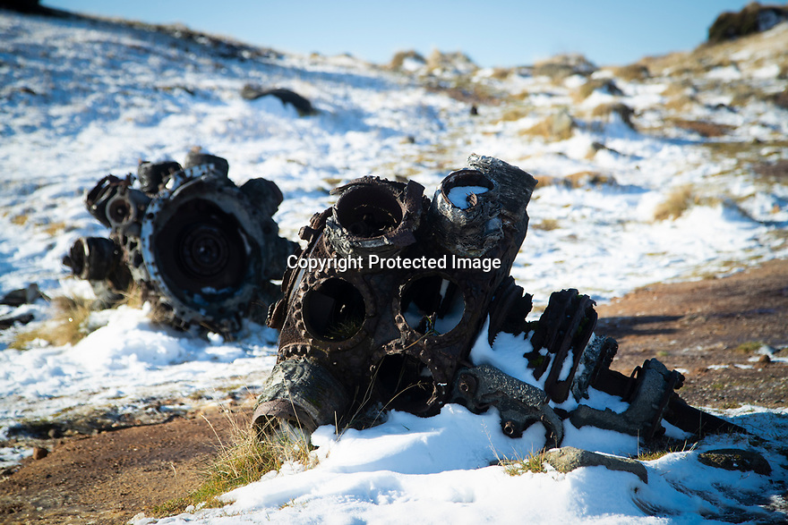 09/11/19<br /> <br /> Whole engines lie at the moorland crash scene.<br />  <br /> Surrounded by fresh overnight snow, hikers gather, in one of the remotest areas of the Derbyshire Peak District, for a two minute silence and to lay wreaths and crosses on the wreckage of an American RB29 bomber, known  as 'Over-Exposed' which crashed on Bleaklow Moor near Higher Shelf Stones, killing all thirteen crew in November 1948. Piles of twisted metal have been piled up to form a makeshift memorial that lies next to whole engines, pieces of fuselage, wings, wheels and other twisted parts of aluminium that have lain on the moors for  71 years.<br /> <br /> Today prayers were said, a harmonica player performed the Last Post and Taps (the US equivalent) and members of the Woodhead Mountain Rescue teams remembered their forbears who were first to arrive at the crash scene after the bomber descended in low cloud hitting the high peak.<br /> <br /> All Rights Reserved: F Stop Press Ltd.  <br /> +44 (0)7765 242650 www.fstoppress.com