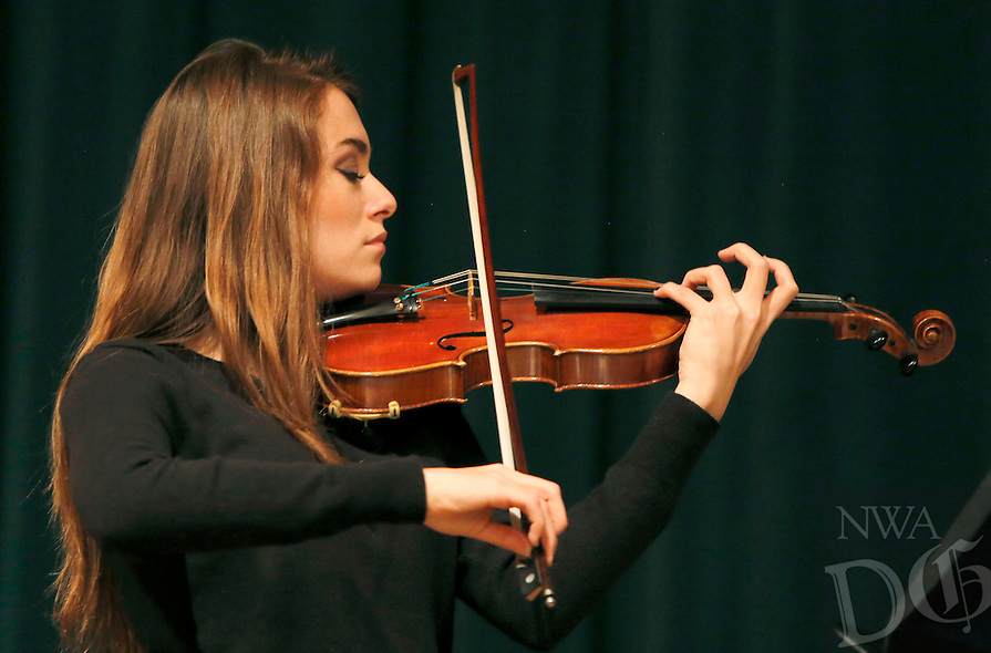 NWA Democrat-Gazette/DAVID GOTTSCHALK  Mary Moreno, a senior at Bentonville High School, performs a portion of the movie score from Shindlers's List with members of the Bentonville High School Chamber Orchestra before George Abraham, a Holocaust survivor, speaks Friday, November 6, 2015, during the 24th Annual Holocaust Conference at the Jones Center in Springdale.