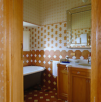 Terracotta tiles line the lower part of this bathroom wall, complimented by a stencilled paint finish above it