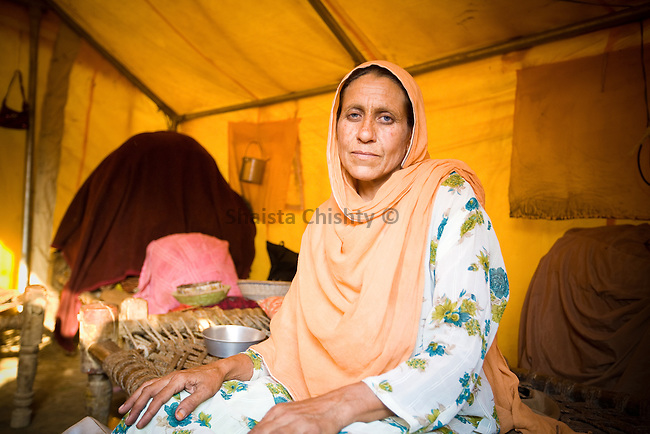 Pakistani woman in her new home, a makeshift tent following the floods in Pakistan, 2010.