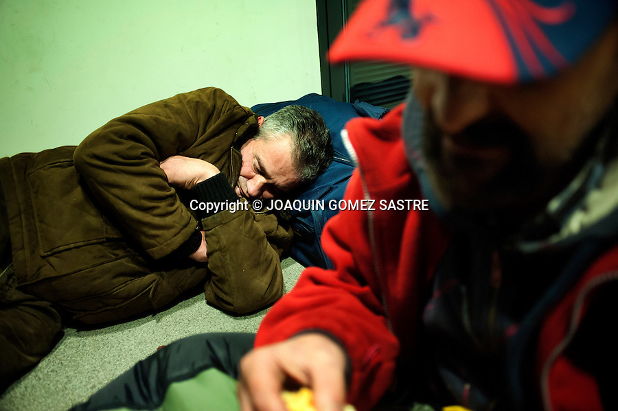 Two homeless people share the ATM where you sleep in Santander (Spain).photo © JOAQUIN GOMEZ SASTRE