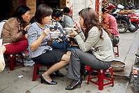 Vietnam. Hanoi. Early morning on a street's restaurant, a group of women, seated on small plastic stools, eat for breakfast a bowl of beef noodle soup, called pho. The pho is a traditional dish of Vietnam. People eat with chopsticks which are a pair of small, equal-length, tapered sticks, used as traditional eating utensils. 08.04.09 © 2009 Didier Ruef