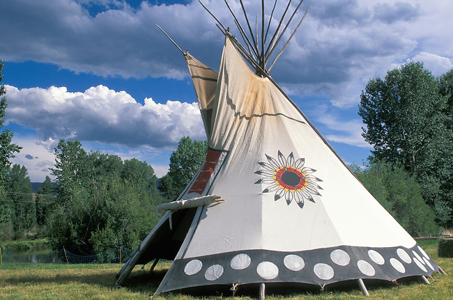 Painted and decorated Blackfeet tepee with the Blackfeet circular symbol and painted dots on the bottom border