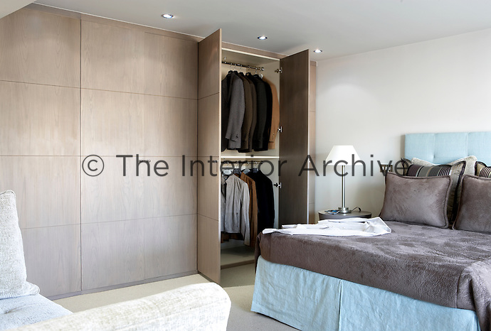 A white bedroom with a floor to ceiling built in wardrobe, where a man's jackets are seen hanging from rails inside. A double bed has a blue valance and headboard and a grey leather like cover.