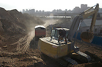 A worker adds oil to a bulldozer in the worksite of the future Olympic Green which will be the main and central district for 2008 Olympic Game in Beijing, China..04-FEB-04