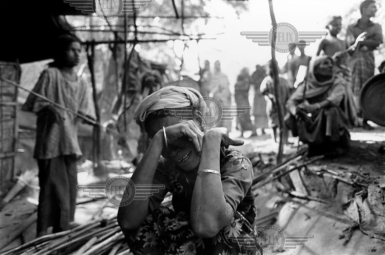 A woman cries as she squats on the ground in the makeshift refugee camp of Dum Dum Mea. Bangladesh is the temporary home to 36,000 Muslims who have fled human - rights abuses and religious persecution in Burma. Dum Dum Mea is home to some 10,000 Rohingyas who live in some of the worst conditions of any refugees in the world.  Bangladesh, like Thailand, is not a signatory to the 1951 Refugee Convention and these people are labelled 'illegal immigrants' despite the fact that they are among the most persecuted of Burma's peoples. /Felix Features