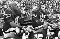 Oakland Raiders lineman Otis Sistrunk and Art Thoms<br />on the sidelines. (1974 photo/by Ron Riesterer)