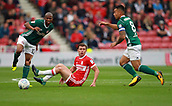 30th September 2017, Riverside Stadium, Middlesbrough, England; EFL Championship football, Middlesbrough versus Brentford; Ben Gibson of Middlesbrough is left on the floor after a challenge with Kamohelo Mokotjo of Brentford and Nico Yennaris in the 2-2 draw