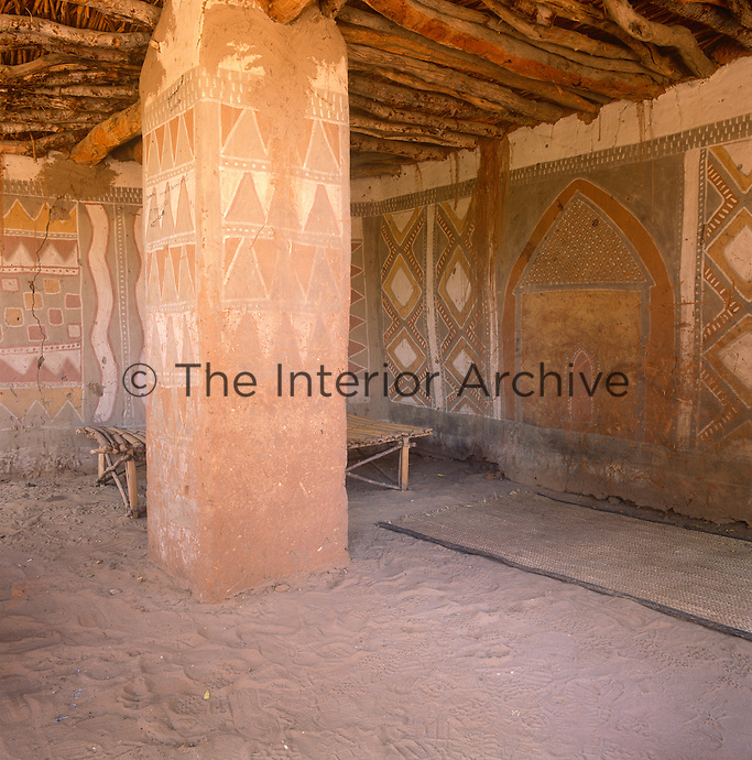 The interior of a traditional Dogon house in Mali with decorative painting on the walls and a rudimentary bed.