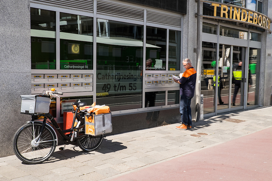 Nederland, Utrecht, 30 mei 2015<br /> Postbezorger van Postnl doet brieven in een brievenbus. Er worden steeds minder brieven per post verstuurd door de digitalisering<br />  <br /> Foto: Michiel Wijnbergh