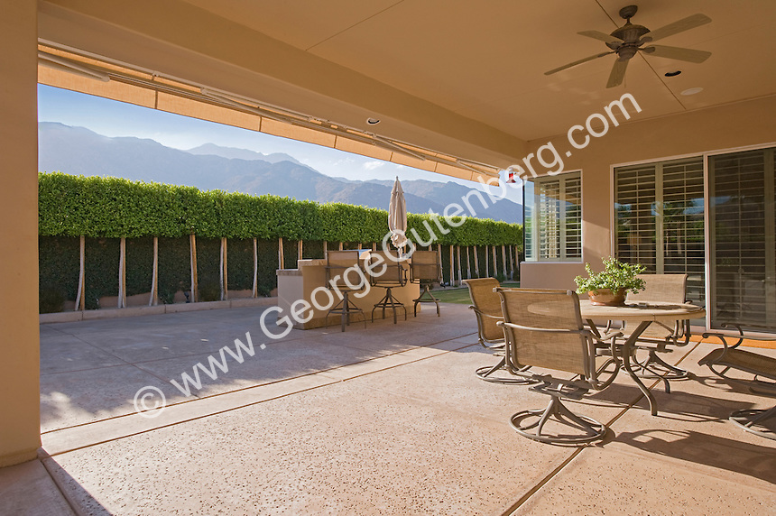 Covered patio overlooks ficus tree hedge and mountains