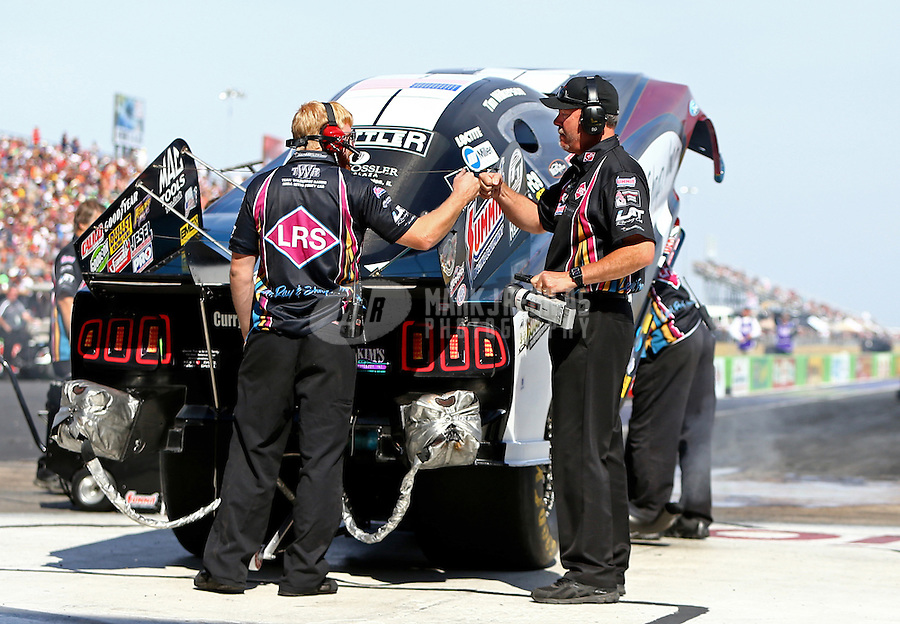 Oct 16, 2015; Ennis, TX, USA; Bob Wilber (right) a crew member for NHRA funny car driver Tim Wilkerson fist bumps a teammate during qualifying for the Fall Nationals at the Texas Motorplex. Mandatory Credit: Mark J. Rebilas-USA TODAY Sports