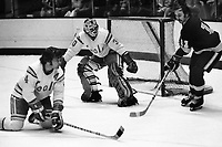 Caption:<br /> Seals vs Los Angeles Kings 1975, Kings #11 Mike Corrigan shot on Gary Simmons, and Bob Stewart.<br /> (photo/Ron Riesterer)