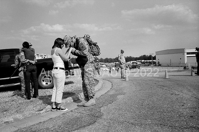 Columbus, Georgia.USA.March 12, 2007..450 soldiers of the third Infantry, third brigade are deployed to Iraq from Fort Benning, Georgia. Many of the men are being deployed for their second or third tour of duty...Soldiers spent their last few minutes with their families on the base before separating and boarding a bus to the base airport...Center - Melinda and Nathan Cencellieri give a lasting hug before Nathan deploys to Iraq...Left - Kimberly Handcock and her husband, Matthew cling to each other in a final embrace moments before he is deployed to Iraq for a second tour.