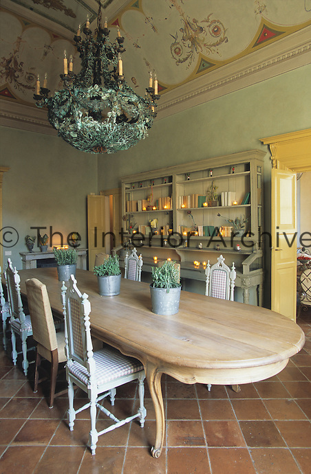 A large oval table dominates the tiled floor of this dining room which has a hand-painted ceiling