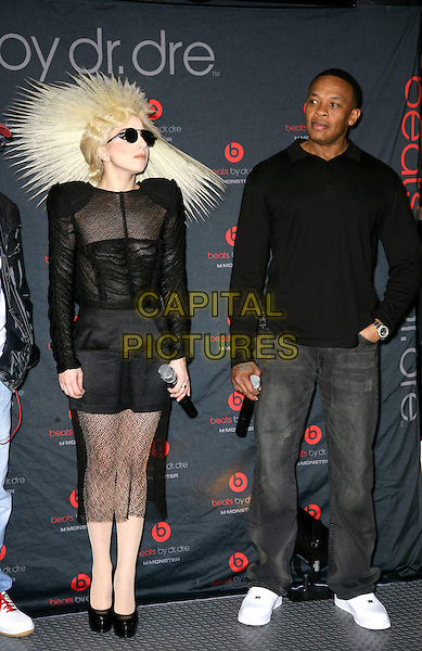 LADY GAGA (Stefani Joanne Angelina Germanotta) & DR. DRE (Andre Romelle Young).attends the 2010 International Consumer Electronics Show (CES), the world's largest annual consumer technology trade show held at The Las Vegas Convention Center, Las Vegas, Nevada, USA, .7th January 2010..full length wig hair sunglasses round black sheer see through thru shoulder pads knitted knit ruched top microphone dress platform shoes jeans white trainers hat hairspray.CAP/ADM/MJT.© MJT/AdMedia/Capital Pictures.