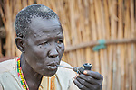 A woman smokes a pipe in Bunj, the host community for the Doro Refugee Camp in Maban County, South Sudan. Doro is one of four camps in Maban that together shelter more than 130,000 refugees from the Blue Nile region of Sudan. Jesuit Refugee Service provides educational and psycho-social services to both refugees and the host community.<br /> <br /> Misean Cara supports the work of JRS in the Maban camps and host community.