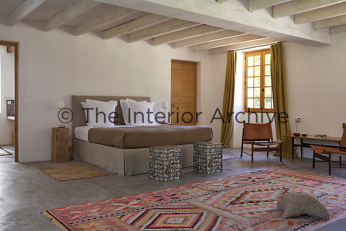 A guest bedroom with Scandinavian chairs and Moroccan rug in Le Pressoir, a 14th century mill converted into holiday lets in the grounds of the Chateau de la Bourlie in the Dordogne