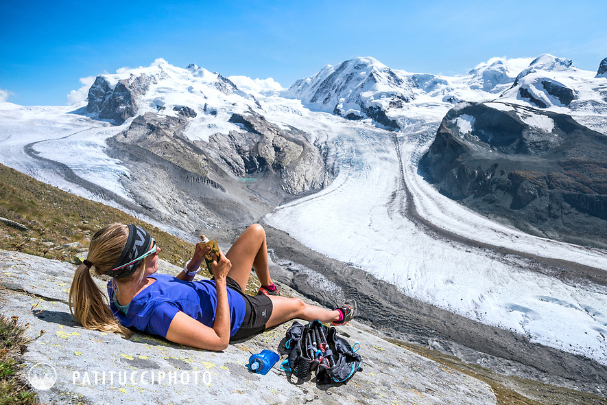 A woman lays eating on a rock while  relaxing in the sun with views of the Monte Rosa, Switzerland.