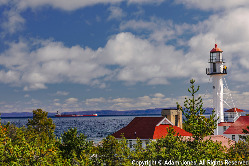 Freighter bound for Canada passing Whitefish Point Lighthouse, the oldest operating light on Lake Superior, Upper Peninsula, Michigan