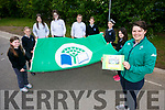 Rugby star Ciara Griffin  raises  the new Green Flag at Scoil Nuachabhail, Ballymac on Friday and shows a picture of her as part of the green flag committee when winning their first geen flag Pictured with the Green Flag committee l-r Aoife Reidy, Jill Quirke, Róisín Reidy, Ciara O'Shea, Shonagh Griffin, Roisin O'Rahilly, Niamh Rice and Holly Geary