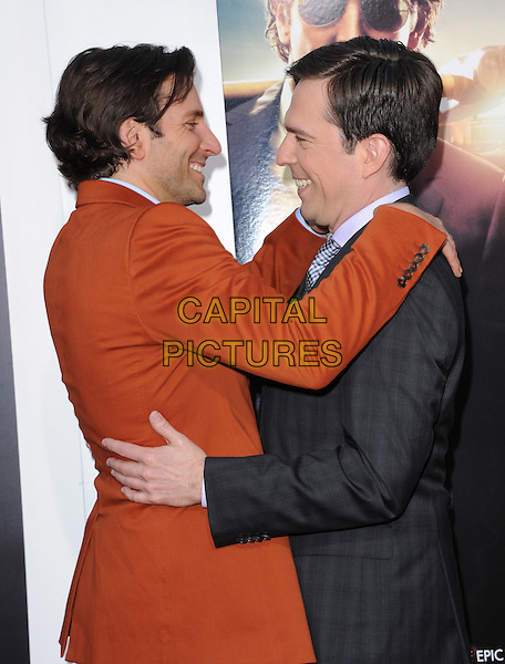 "Bradley Cooper & Ed Helms.""The Hangover Part III"" Los Angeles Premiere held at the Westwood Village Theater, Los Angeles, California, USA..May 20th, 2013.half length side profile black arms around on shoulders hug embrace orange suit blue shirt                                      .CAP/DVS.©DVS/Capital Pictures"