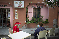 Italy. Liguria Region. Bordighera. Two elderly women seat on a the terrace of a closed bar. They both wear masks to protect themselves from the Coronavirus (also called Covid-19). The safety sanitary measures advocate people to stand apart in order to avoid close contact and potential contamination by coronavirus. Liguria is a region of north-western Italy. Bordighera is a town and comune in the Province of Imperia. 19.07.2020 © 2020 Didier Ruef