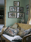 A detail of a traditional green bedroom showing a bamboo cane sofa richly embroidered cushions