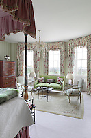 One of the light and airy bedrooms, decorated with floral print curtains and antique furniture, including a Regency four-poster bed