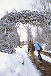 A young couple walks under an antler arch on the town square in Jackson, Wyoming.