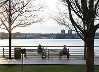 New York, New York City, during the time of Coronavirus. People social distancing while sitting on park benches by the Hudson River.