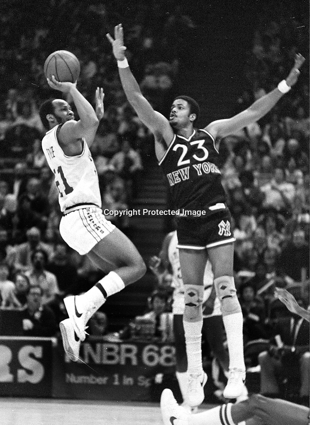 Warriors Lloyd B. Free shoting over New York Knicks Maurice Lucas #23.....(1982 photo/Ron Riesterer)