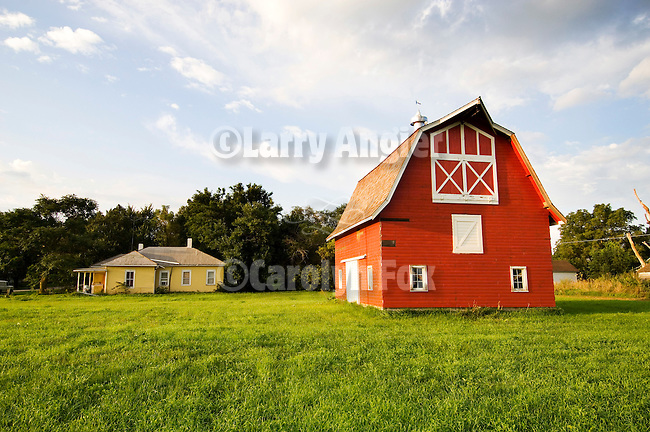 Red barn with white trim, weather vane on cupola in front of a pale yellow farm house