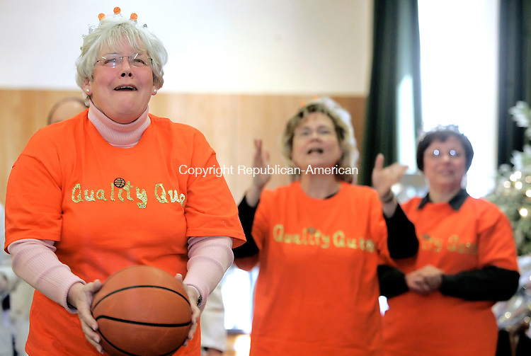 WATERBURY, CT--05 March 2007--030507JS06-Donita Semple, with the Quality Management team, aims for the basket while teammates Ginny Potrepka and Dianna Kiraly cheer her on during Waterbury Hospital's 4th annual March Madness basketball event held at the hospital on Monday. The annual event is run by the Waterbury Hospital Morale Booster Club and featured a hospital-wide basketball shootout competition. Also on hand at the event was former UConn stand-out Maira Conoln who is now an assistant coach for the Southern Connecticut State University's women's basketball team. <br /> Jim Shannon / Republican-American