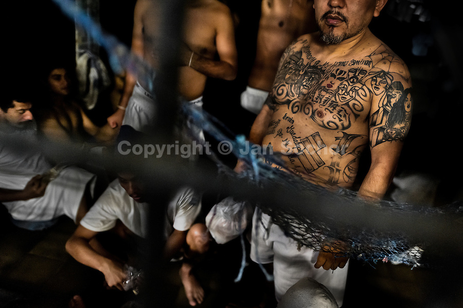 "Members of the Mara Salvatrucha gang (MS-13) are seen behind the bars in an overcrowded cell at the detention center in San Salvador, El Salvador, 20 February 2014. Although the country's two major gangs reached a truce in 2012, the police holding cells currently house more than 3000 inmates, five times more than the official built capacity. Partly because the ordinary Mara gang members did not break with their criminal activities (extortion, street-level distribution of drugs, etc.), partly because Salvadorean police still applies controversial anti-gang law which allows to detain almost anyone for ""suspicion of gang membership"". Accused young men are held in police detention centers where up to 25 inmates may share a cell of five-by-five metres. Here, in the dark overcrowded cages, under harsh and life-threatening conditions, suspected gang members wait long months, sometimes years, for trial or for to be transported to a regular prison."