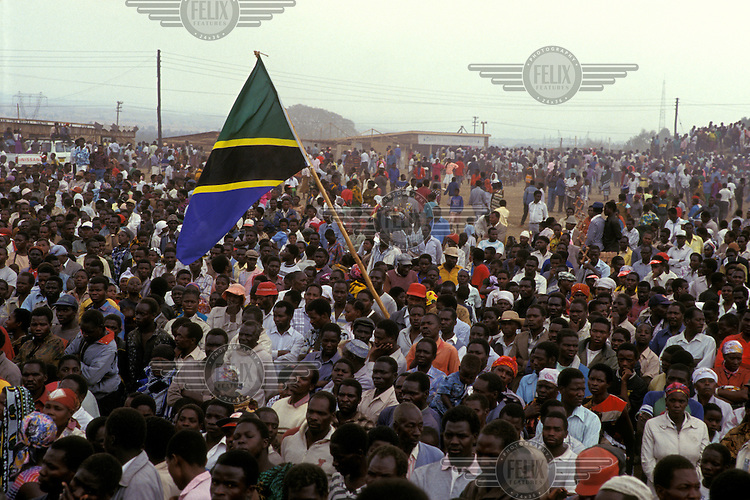 Crowds with national flag at a political rally.