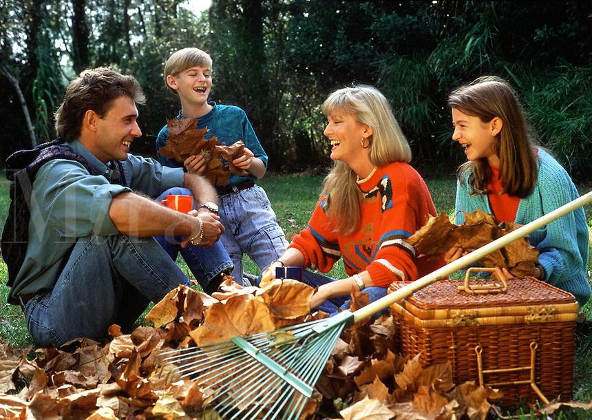 A smiling family takes a beak from raking leaves.