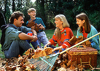 A smiling family takes a beak from raking leaves.