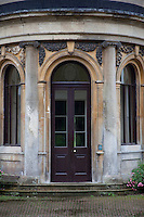 Decorative stonework swags and pilasters adorn the double doors leading into the hall from the garden
