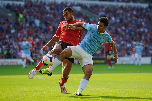 25.08.2013 Cardiff, Wales. Cardiff Defender Steven Caulker challenges Man City Forward Sergio Aguero during the second half of the Barclays Premier League football match between Cardiff City and Manchester City at Cardiff City Stadium.
