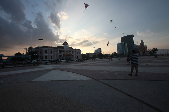 People fly kites on the beach-front plaza as the sun begins to set in Nha Trang, Vietnam. July 8, 2011.