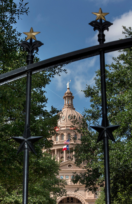 The late 19th century gates and accompanying fencing designed for the perimeter of the Texas State Capitol in 1888 by William Munro Johnson. The wrought-and-cast iron fencing uniquely features gilt and black lone stars, with the gates centered by the Texas State Seal  - Stock Image.