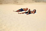 TWO MEN RELAX AND NAP IN THE SAND IN CABO SAN LUCAS