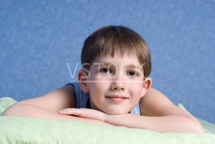 Boy (12-13) lying on bed