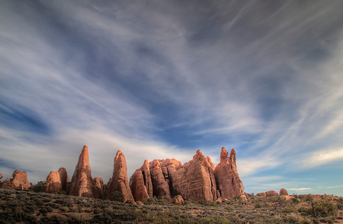 Cirrus clouds float above the sandstone fins at Arches National Park, Utah