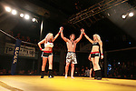 Jake Morris is victorious once again having his arms raised by two beauties after defeated his opponent in the first round.