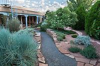 Gravel path between flagstone garden walls in drought tolerant backyard New Mexico garden, design by Judith Phillips
